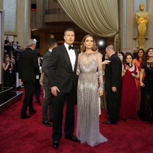 Angelina Jolie stunned in head- to- toe sparkles, favoring the conservative route over 2012's Jessica Rabbit leg. Here she is with her Number One Accessory, Brad Pitt. Designer: Elie Saab